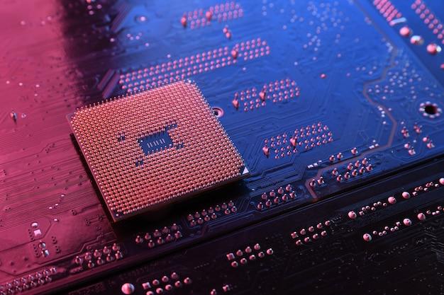Computer-cpu-prozessorchip auf leiterplatte, motherboard-hintergrund. nahansicht. mit rot-blauer beleuchtung.