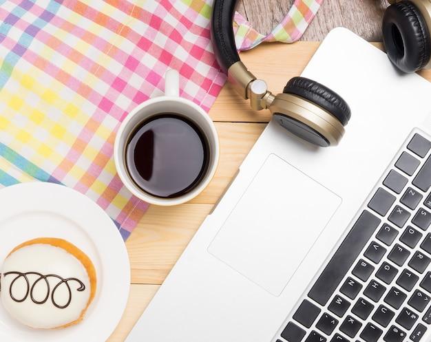 Computer, der im café mit kaffee und donut arbeitet