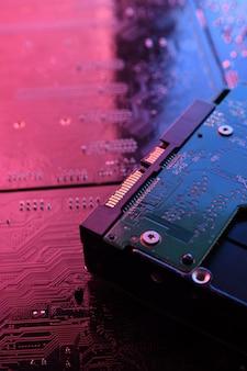 Computer festplattenlaufwerke festplatte, ssd auf leiterplatte, hauptplatine. nahansicht. mit rot-blauer beleuchtung