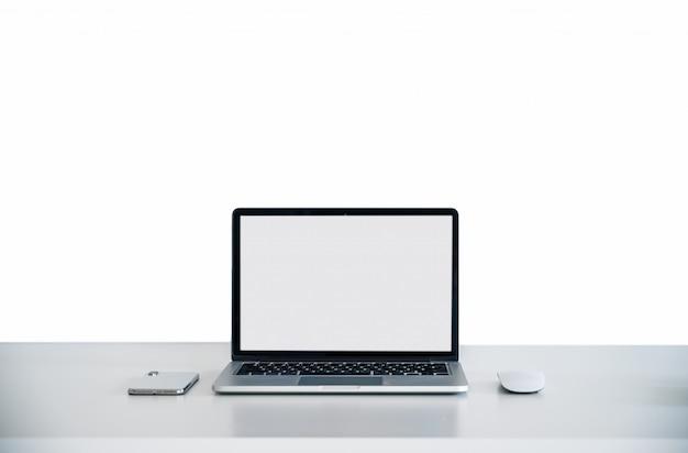 Computer-laptop auf dem weißen tisch mit weißem bildschirm