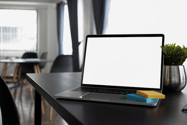 Computer-laptop, haftnotiz und zimmerpflanze auf schwarzem holztisch.