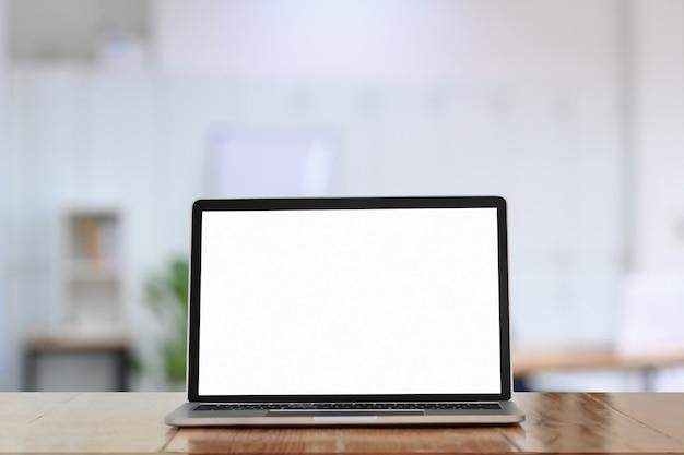 Computer-laptop mit weißem bildschirm auf holztisch im büro.