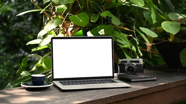 Computer-laptop mit weißem bildschirm, kaffeetasse und kamera auf holztisch im grünen garten.