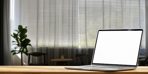 Computer-laptop mit weißem leerem bildschirm, der hölzernen schreibtisch über wohnzimmer setzt.