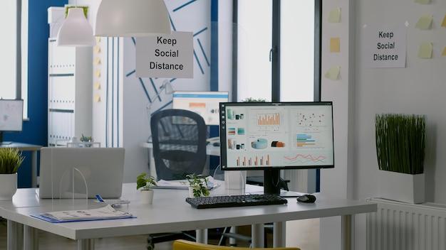Computer mit finanzdaten im modernen bürointerieur mit zeichen für soziale distanz an den wänden und kunststofftrennern. leerer firmenraum mit niemandem drin