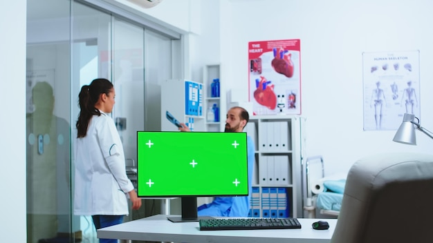 Computer mit grünem bildschirm im krankenhausschrank und arzt, der das röntgen des patienten überprüft. desktop mit austauschbarem bildschirm in der medizinischen klinik, während der arzt die röntgenaufnahme des patienten auf diagnose überprüft.