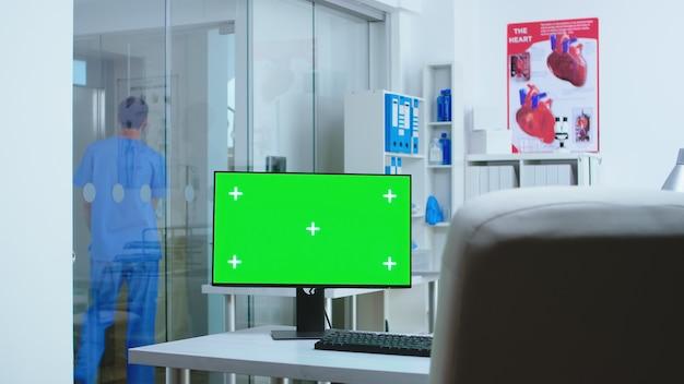 Computer mit kopienraum im krankenhaus und assistent, der in den aufzug geht. desktop mit leerem greenscreen-mockup, isolierter platz für medizinspezialisten im klinikschrank.