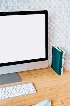 Computer mit leerem weißem bildschirm auf hölzernem schreibtisch