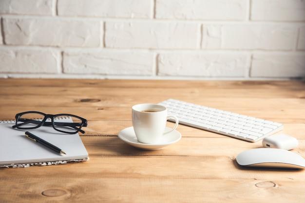 Computer mit notizblock und kaffee auf dem tisch