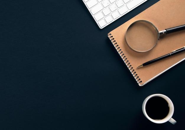 Computer mit notizblock und kaffee auf schwarzem bürotisch