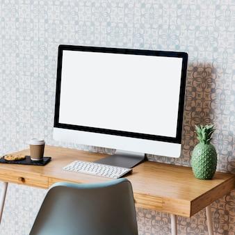 Computer mit plätzchen und beseitigung höhlen auf hölzernem schreibtisch aus