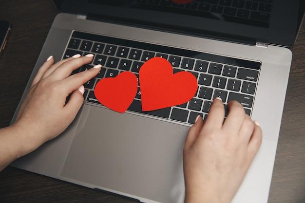 Computer mit roten herzen auf dem tisch