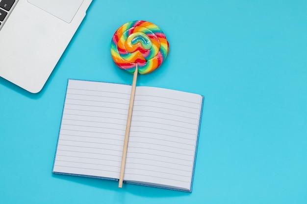 Computer, süßigkeiten und taschenbuch auf blauem hintergrund