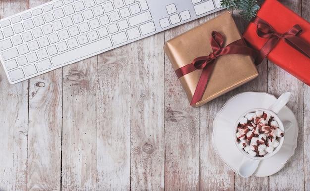 Computer-tastatur, weihnachtsgeschenk und eine tasse mit marshmallows