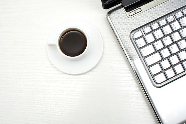 Computer und kaffee im bürotisch