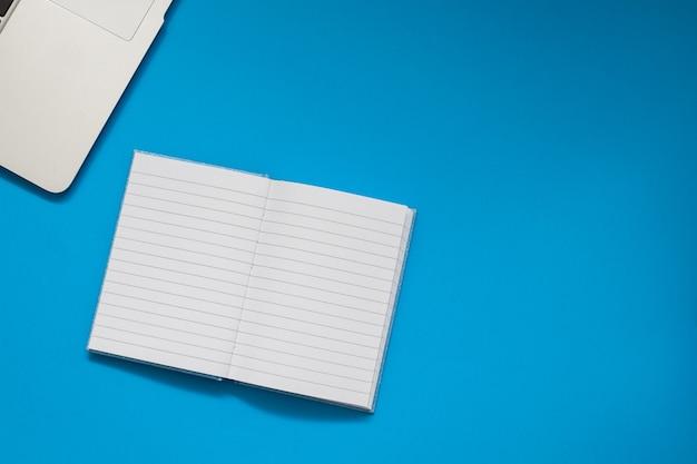 Computer und taschenbuch auf blauem hintergrund