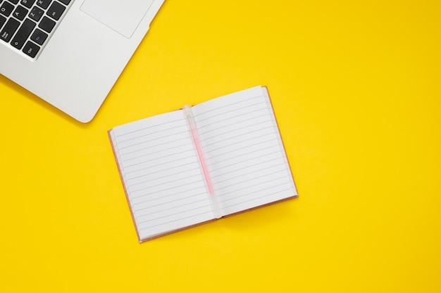 Computer und taschenbuch auf gelbem hintergrund