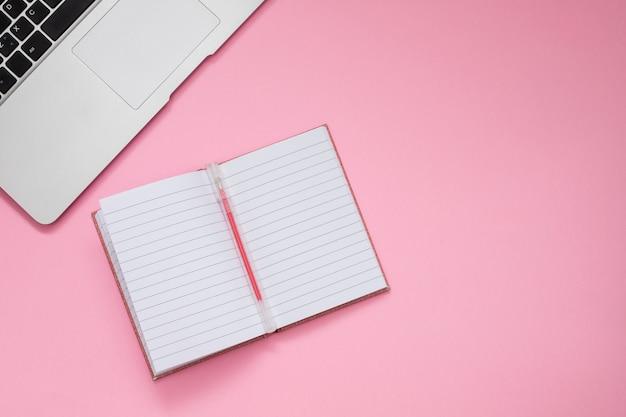 Computer und taschenbuch auf rosa hintergrund