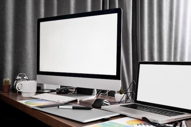 Computerbildschirm und laptop-gerät auf büroarbeitsplatz
