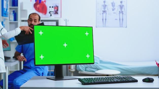 Computerdisplay mit kopienraum im krankenhausschrank und arzt mit röntgenaufnahme. desktop mit austauschbarem grünem bildschirm in der medizinischen klinik, während der arzt die röntgenaufnahme des patienten auf diagnose überprüft