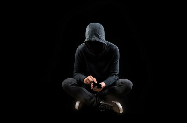 Computerhacker mit handy smartphone daten stehlend