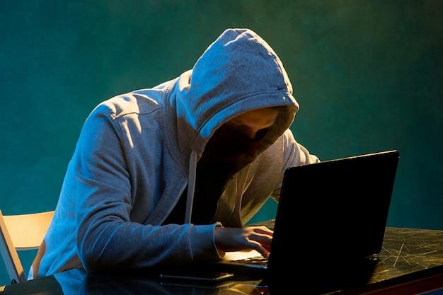 Computerhacker mit kapuze, der informationen mit laptop stiehlt