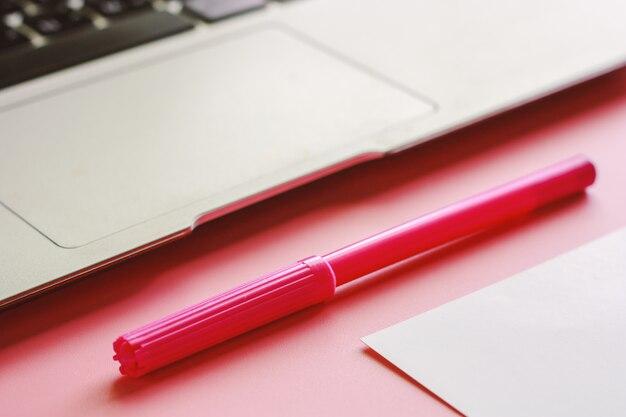 Computerlaptop mit einem stift und einem weißbuch und auf rosa farbhintergrund