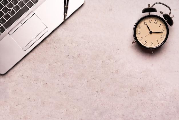 Computerlaptop mit schwarzer uhr auf draufsicht der draufsicht der arbeitstischflachenzusammensetzung