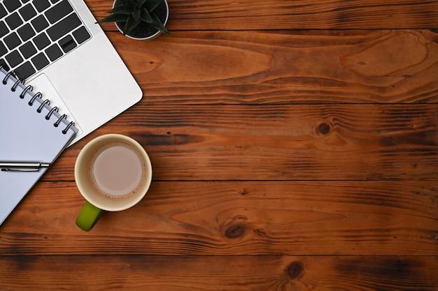 Computerlaptop, notizbuch und kaffeetasse auf schreibtisch aus holz.