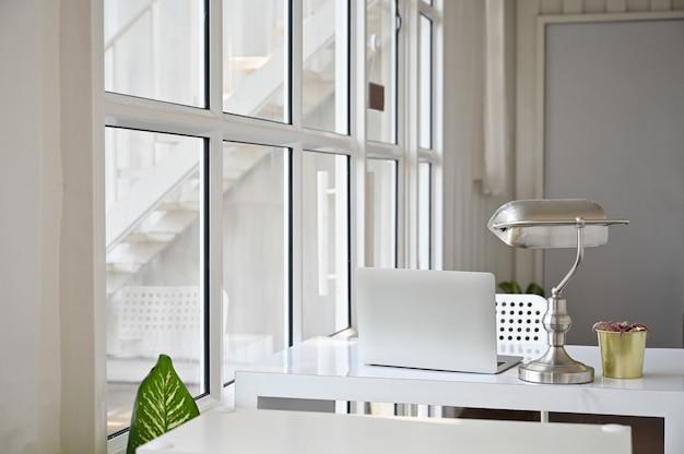 Computerlaptop und -lampe auf bürotisch in den büroräumen.