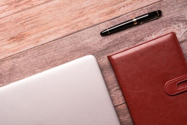 Computerlaptop und -notizbuch auf draufsicht der tischplatte der arbeitsebene