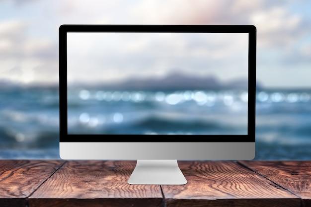 Computermonitor mit unscharfem bild des meeres auf einem holztisch gegen dasselbe mit bokeh, kopienraum. arbeiten an der küste, an der natur, außerhalb des bürokonzepts.