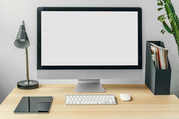 Computermonitor mit weißem schirm des modells auf bürotisch mit versorgungen