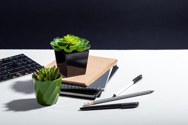 Computernotizblöcke und saftige blumen. tastaturbriefpapier am home-office-arbeitsplatz für remote-arbeit. weißer home-office-tisch mit kopienraum auf schwarzem hintergrund mit tischlampenschatten.