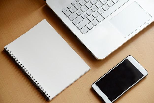 Computernotizbuch mit smartphone und notizbuch auf hölzernem