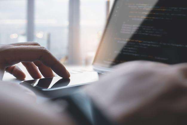 Computerprogrammierer mobiler app-entwickler mit mobiltelefon und codierung von javascript auf laptop