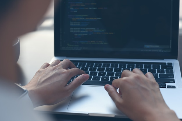 Computerprogrammierer software-ingenieur, der javascript auf laptop codiert