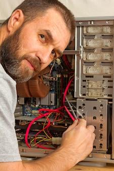 Computerreparatur. ein mann mit bart fixiert die systemeinheit