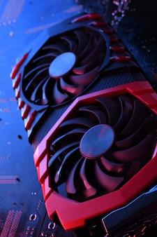Computerspiel-grafikkarte, grafikkarte mit zwei kühlern auf der platine, motherboard-hintergrund. nahansicht. mit rot-blauer beleuchtung.