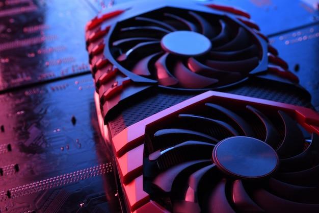 Computerspiel-grafikkarte, videokarte mit zwei kühlern auf leiterplatte, motherboard-hintergrund. nahansicht. mit rot-blau eine beleuchtung.