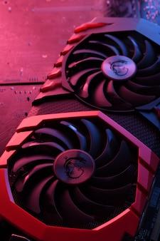 Computerspiel-grafikkarte, videokarte mit zwei kühlern auf leiterplatte, motherboard-hintergrund. nahansicht. mit rot-blauer beleuchtung.