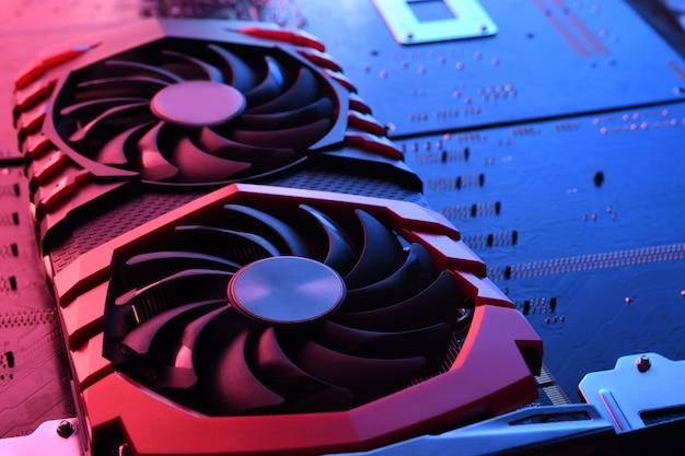 Computerspiel-grafikkarte, videokarte mit zwei kühlern auf leiterplatte, motherboard-hintergrund.