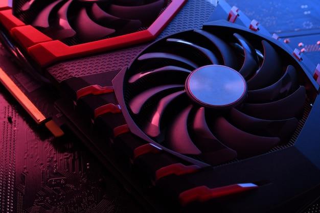 Computerspiel-grafikkarte, videokarte mit zwei kühlern auf leiterplatte, motherboard-tisch. nahaufnahme. mit rot-blauer beleuchtung.