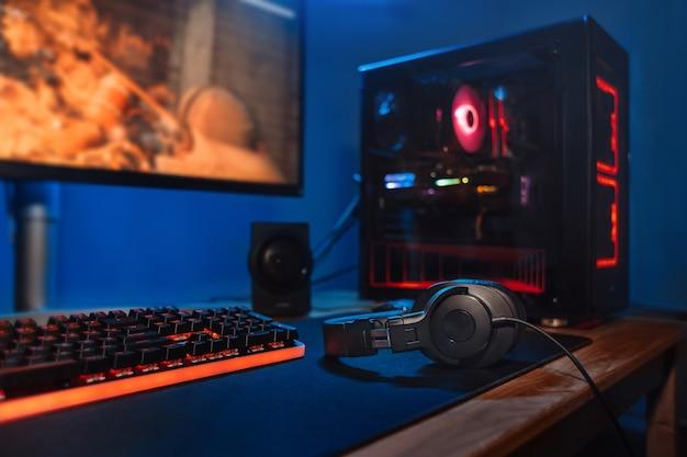 Computerspieler-arbeitsplatz mit neuer spieletastatur, maus, kopfhörern, modernem pc mit verschwommenem blauem und rotem neonlicht.