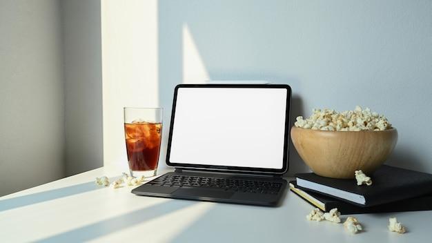 Computertablett mit leerem bildschirm und einer schüssel popcorn auf weißem tisch.