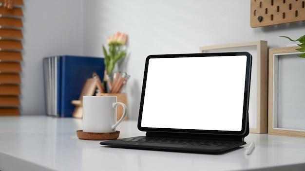 Computertablette mit leerem bildschirm, kaffeetasse und zubehör auf weißem schreibtisch.