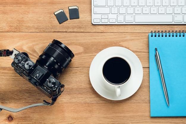 Computertastatur, stift und notizblock für notizen, kaffeetasse, flash-laufwerke und kamera auf einem holztisch. gegenstände des fotografen am arbeitsplatz.