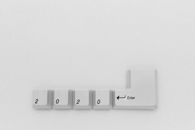 Computertasten mit 2020 kommen geschrieben unter verwendung der weißen knöpfe auf weißem hintergrund herein