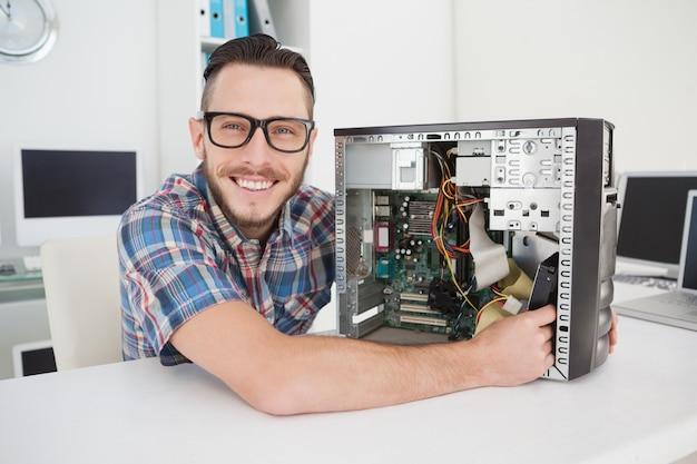 Computertechniker, der an der defekten konsole lächelt an der kamera arbeitet