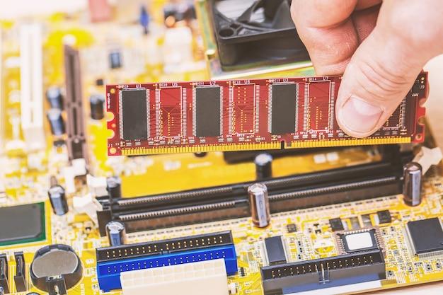 Computertechniker, der computerspeicher ram im schlitz des motherboards installiert